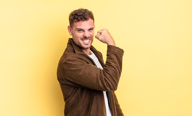 Jeune bel homme hispanique se sentant heureux, satisfait et puissant, ajustement flexible et biceps musclés, ayant l'air fort après la salle de gym