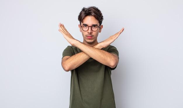 Jeune bel homme hispanique semblant ennuyé et malade de votre attitude, en disant assez! les mains croisées devant, vous disant d'arrêter