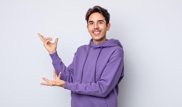 Jeune bel homme hispanique souriant joyeusement donnant un câlin de bienvenue chaleureux, amical et affectueux, se sentant heureux et adorable