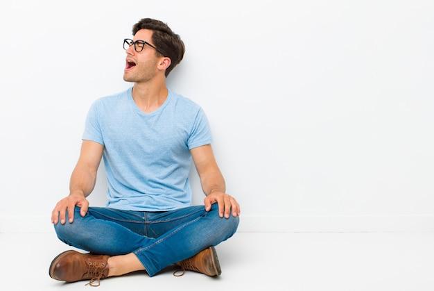 Jeune bel homme hurlant furieusement, criant agressivement, l'air stressé et en colère assis sur le sol