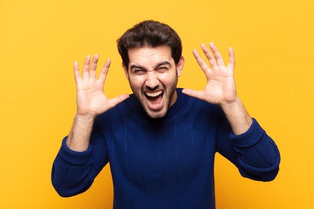 Jeune bel homme hurlant de panique ou de colère, choqué, terrifié ou furieux, avec les mains à côté de la tête