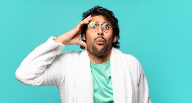 Jeune bel homme indien à l'air heureux, étonné et surpris, souriant et réalisant de bonnes nouvelles incroyables et incroyables et portant un peignoir