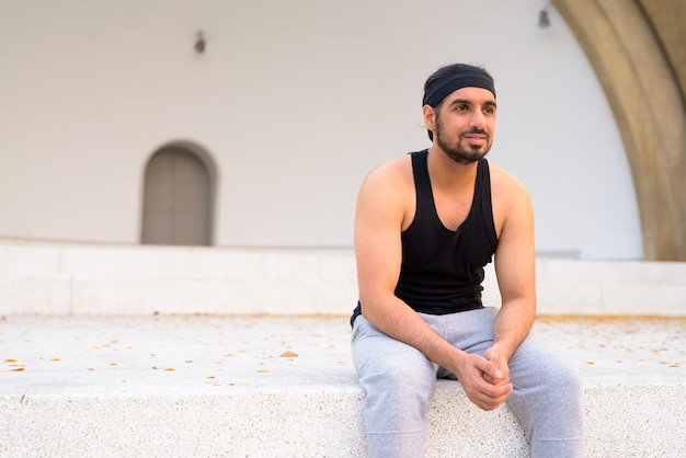 Jeune bel homme indien barbu pensant alors qu'il était assis dans les rues à l'extérieur