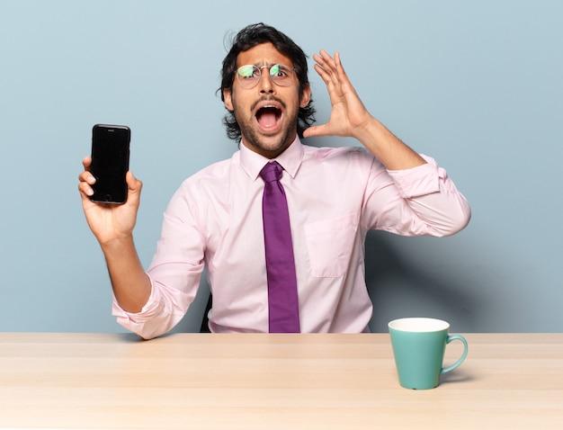 Jeune bel homme indien criant avec les mains en l'air, se sentant furieux, frustré, stressé et bouleversé. concept d'entreprise