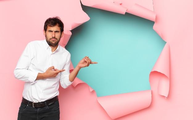 Jeune bel homme indien expression en colère contre fond de trou de papier cassé