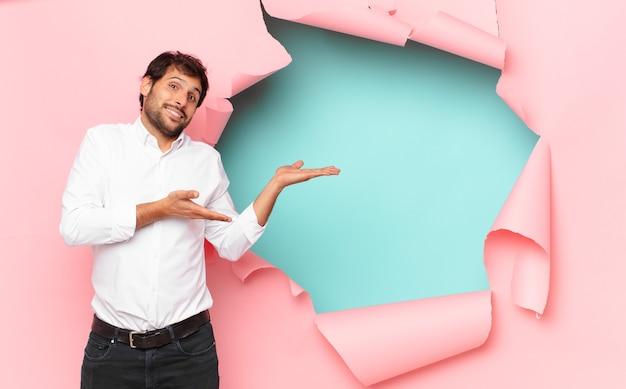 Jeune bel homme indien expression heureuse sur fond de trou de papier cassé