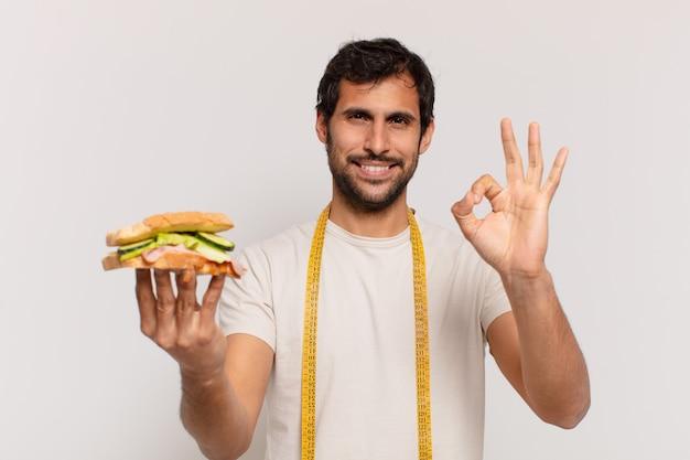 Jeune bel homme indien expression heureuse et tenant un sandwich