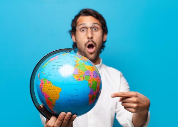 Jeune bel homme indien avec globe terrestre