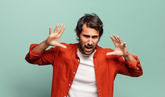 Jeune bel homme indien hurlant de panique ou de colère, choqué, terrifié ou furieux, avec les mains à côté de la tête