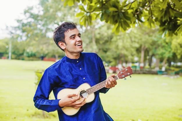 Jeune bel homme indien jouant de la guitare ukulélé dans le parc