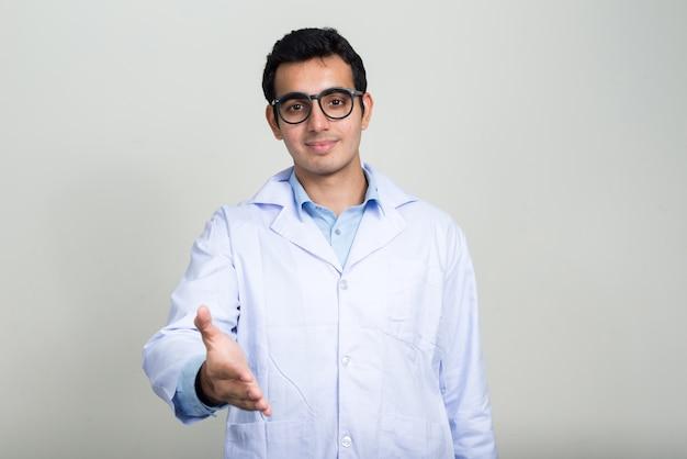 Jeune bel homme indien médecin contre le mur blanc