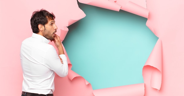 Jeune bel homme indien pensant à l'expression sur fond de trou de papier cassé