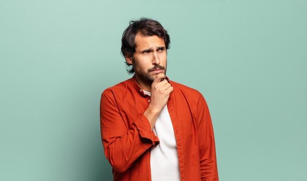 Jeune bel homme indien pensant, se sentant douteux et confus, avec différentes options, se demandant quelle décision prendre