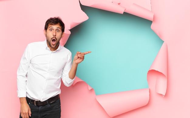 Jeune bel homme indien peur expression contre fond de trou de papier cassé