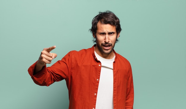 Jeune bel homme indien pointant la caméra avec une expression agressive en colère ressemblant à un patron fou furieux