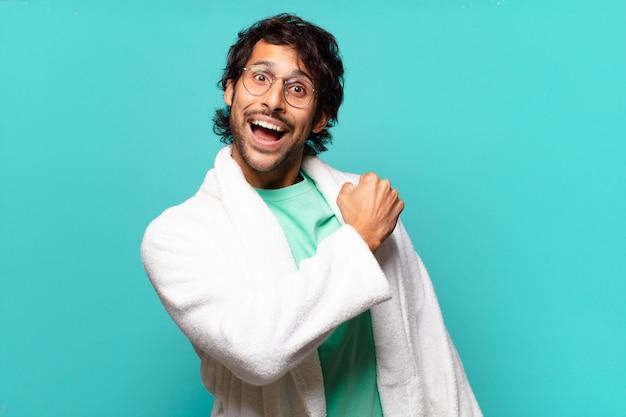 Jeune bel homme indien se sentant heureux, positif et prospère, motivé face à un défi ou célébrant de bons résultats et portant un peignoir de bain