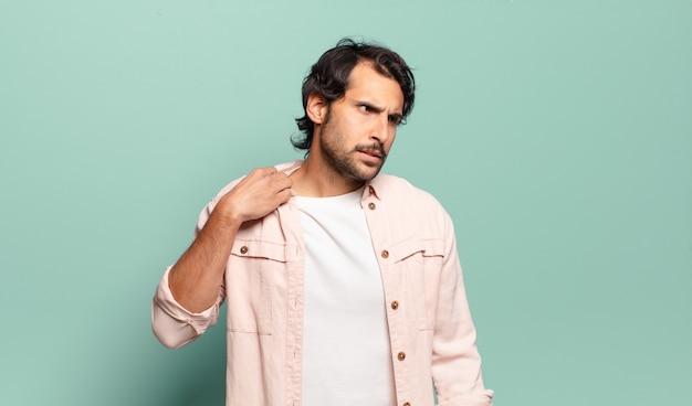 Jeune bel homme indien se sentant stressé, anxieux, fatigué et frustré, tirant le cou de chemise