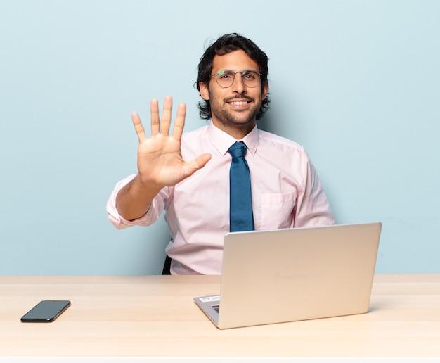 Jeune bel homme indien souriant et à la recherche amicale, montrant le numéro cinq ou cinquième avec la main en avant, compte à rebours. concept d & # 39; entreprise et frelancer