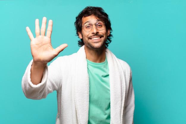 Jeune bel homme indien souriant et à la sympathique, montrant le numéro cinq ou cinquième avec la main en avant, compte à rebours et portant un peignoir