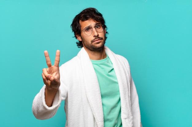 Jeune bel homme indien souriant et à la sympathique, montrant le numéro deux ou seconde avec la main en avant, compte à rebours et portant un peignoir