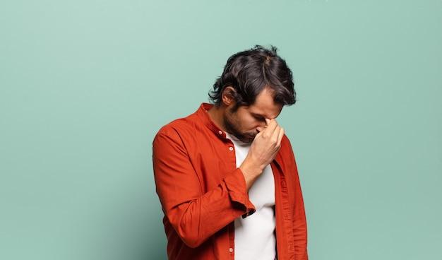 Jeune bel homme indien stressé, malheureux et frustré, touchant le front et souffrant de migraine de maux de tête sévères