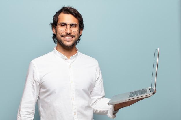 Jeune bel homme indien tenant un ordinateur portable. concept d'entreprise ou de médias sociaux