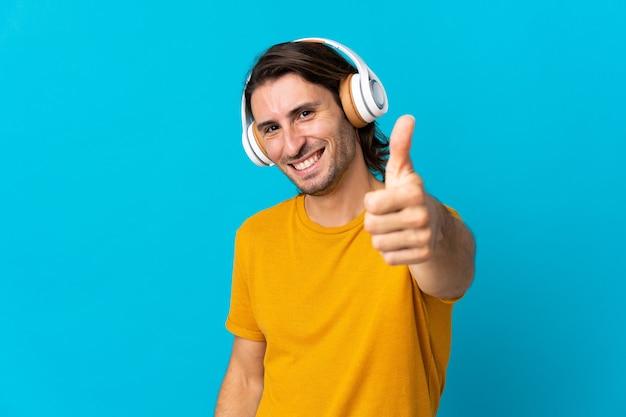 Jeune bel homme isolé sur bleu écoute de la musique et avec le pouce vers le haut