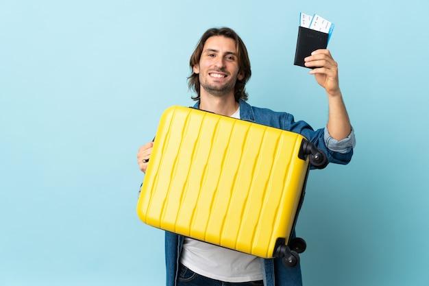Jeune bel homme isolé sur bleu en vacances avec valise et passeport