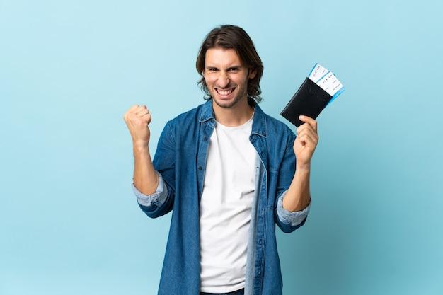 Jeune bel homme isolé sur fond bleu heureux en vacances avec passeport et billets d'avion