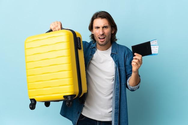 Jeune bel homme isolé sur fond bleu malheureux en vacances avec valise et passeport