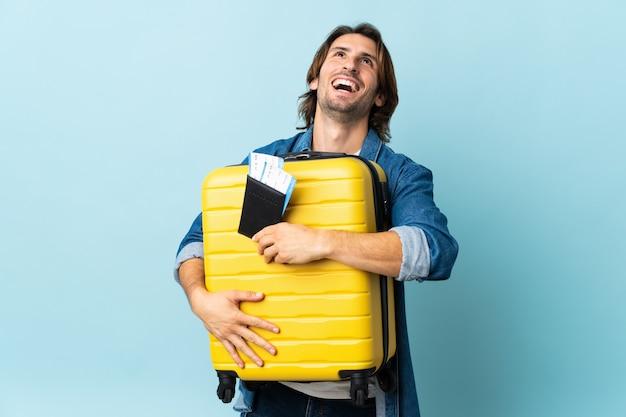 Jeune bel homme isolé sur fond bleu en vacances avec valise et passeport