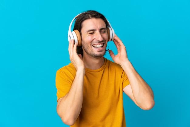 Jeune bel homme isolé sur mur bleu écoute de la musique et du chant