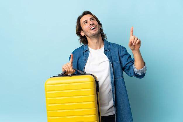 Jeune bel homme isolé sur un mur bleu en vacances avec valise de voyage et pointant vers le haut