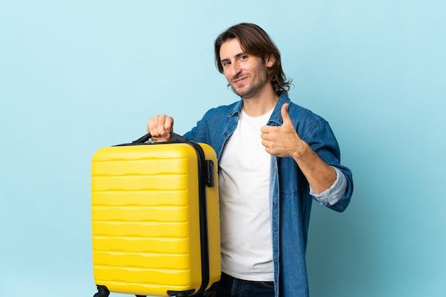 Jeune bel homme isolé sur un mur bleu en vacances avec valise de voyage et avec le pouce vers le haut