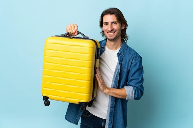Jeune bel homme isolé sur un mur bleu en vacances avec valise de voyage