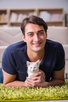 Jeune bel homme jouant avec un chaton blanc