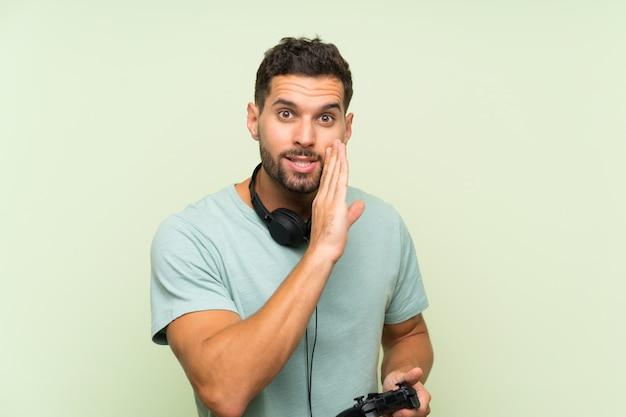 Jeune bel homme jouant avec un contrôleur de jeu vidéo sur mur vert isolé murmurant quelque chose