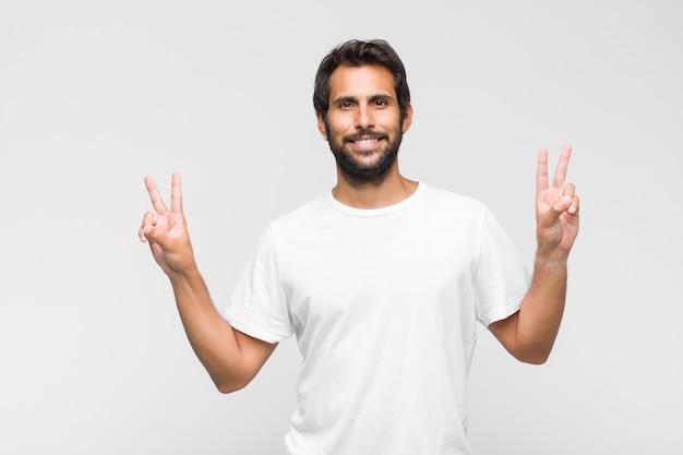 Jeune bel homme latin souriant et à la recherche de bonheur, amical et satisfait, faisant des gestes la victoire ou la paix à deux mains