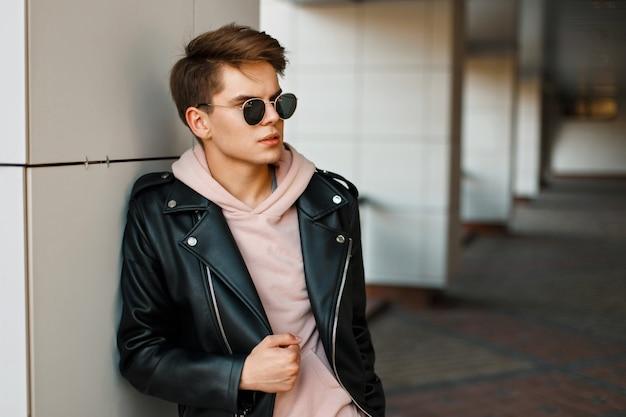 Jeune bel homme en lunettes de soleil aviateur dans une veste en cuir noir et un sweat-shirt rose près d'un mur blanc moderne