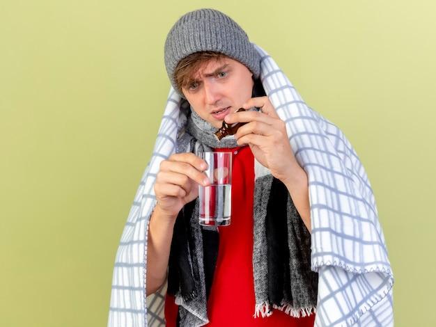 Jeune bel homme malade blonde portant un chapeau d'hiver et une écharpe enveloppée dans un plaid verser le médicament en verre dans un verre d'eau isolé sur fond vert olive avec espace de copie