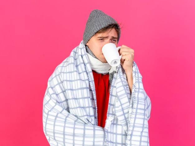 Jeune bel homme malade blonde portant un chapeau d'hiver et une écharpe enveloppée dans une tasse de thé à boire à carreaux à côté isolé sur fond cramoisi avec espace copie