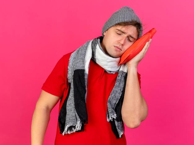 Jeune bel homme malade blonde portant un chapeau d'hiver et une écharpe tenant une bouteille d'eau chaude touchant le visage avec elle avec les yeux fermés isolé sur un mur rose