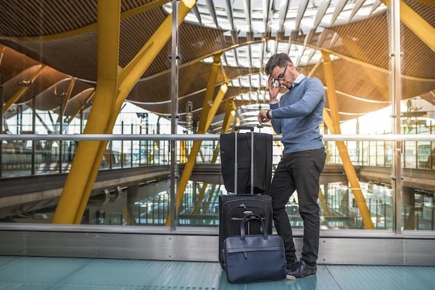 Jeune bel homme malheureux bouleversé à l'aéroport en attendant son vol retardé avec des bagages