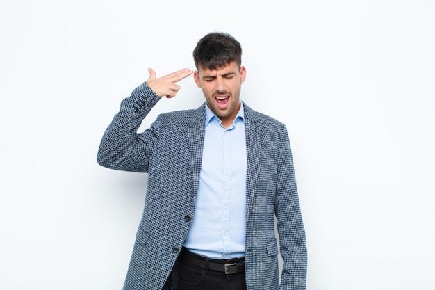 Jeune bel homme malheureux et stressé, geste de suicide faisant signe de pistolet avec la main, pointant la tête sur le mur blanc