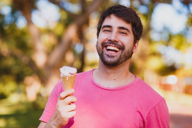 Jeune bel homme mangeant de la glace dans le parc