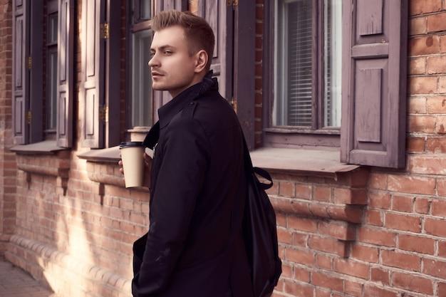 Jeune bel homme en manteau sombre avec une tasse de café