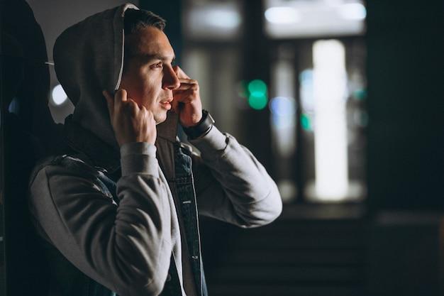 Jeune bel homme marchant le soir en dehors de la rue