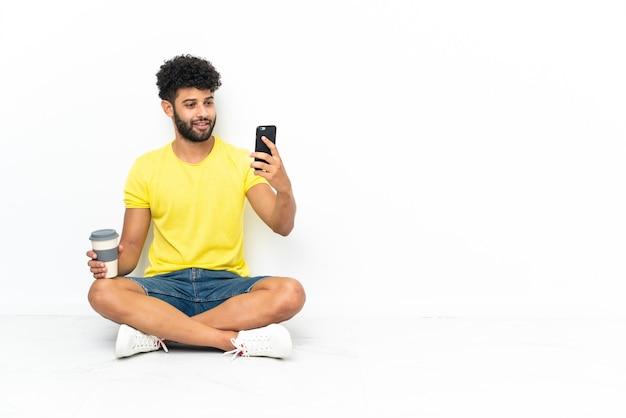 Jeune bel homme marocain assis sur le sol sur fond isolé tenant du café à emporter et un mobile