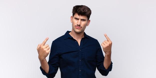 Jeune bel homme avec une mauvaise attitude à la fierté et agressif, pointant vers le haut ou faisant signe amusant avec les mains