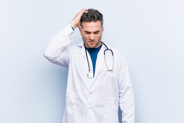 Jeune bel homme médecin fatigué et très somnolent en gardant la main sur la tête.